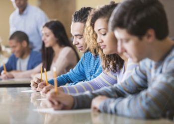 Multi-ethnic group of high school or university students taking test in classroom.  Focus young man in middle of image.