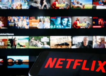 PARIS, FRANCE - MARCH 28: In this photo illustration, the Netflix media service provider's logo is displayed on the screen of an iPhone in front of a television screen on March 28, 2020 in Paris, France. Faced with the coronavirus crisis, Netflix will reduce visual quality for the next 30 days, in order to limit its use of bandwidth. (Photo Illustration by Chesnot/Getty Images)