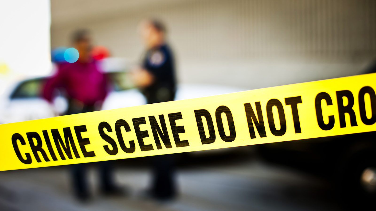 Closeup of crime scene tape with police officers and police car in background. Utahlypse 2011